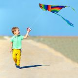 Boy playing with kite on summer field Royalty Free Stock Images