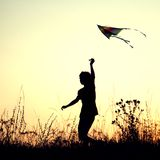 Boy playing kite on summer sunset meadow silhouetted.  stock images