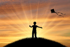 Boy playing with kite on sunset Royalty Free Stock Photography