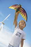Boy Playing With Kite At Wind Farm. Low angle view of a cute little boy playing with dragon kite at wind farm Stock Photography