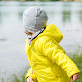 Boy is playing on a lake shore Stock Photography