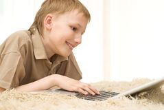 Boy playing on a laptop Stock Image