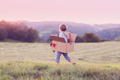 Boy playing with a large box aeroplane outside. Boy playing with his paper plane running on a meadow, pretending he is flying royalty free stock photos