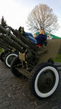 The boy is playing on a large heavy cannon from the times of World War II on the monument to Soviet soldiers Stock Image