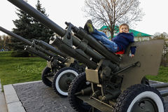 The boy is playing on a large heavy cannon from the times of World War II on the monument to Soviet soldiers Royalty Free Stock Image