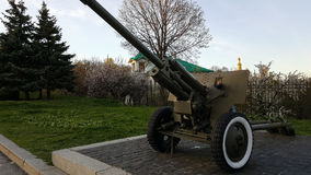 The boy is playing on a large heavy cannon from the times of World War II on the monument to Soviet soldiers Stock Images