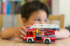 Boy playing with Lego fire truck Royalty Free Stock Image
