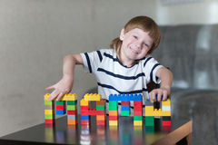 Boy playing with lots of colorful plastic blocks indoor royalty free stock image