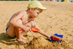 Boy playing with a machine in the sand stock image