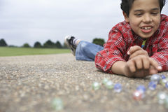 Boy Playing Marbles On Playground Royalty Free Stock Images