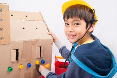 Boy playing mechanic building paper house. Little boy pretend as a mechanic use tools fix the paper house royalty free stock images