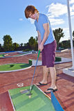 Boy playing mini golf in the course Stock Images