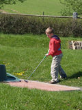 Boy playing minigolf Royalty Free Stock Images