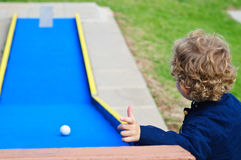 Boy playing in minigolf Stock Photography