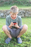 Boy playing with mobil phone Royalty Free Stock Photos