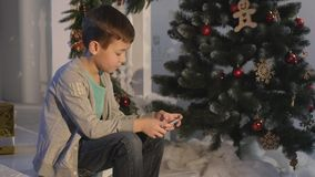 Boy playing in the mobile phone,children and smartphone near Christmas tree stock video footage