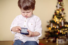 Boy playing with mobile phone. In front of a Christmas tree Stock Images