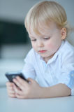 Boy is playing with a mobile phone Royalty Free Stock Images