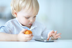 Boy is playing with a mobile phone Stock Photos