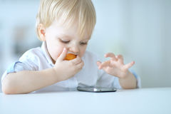 Boy is playing with a mobile phone Stock Images