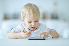 Boy is playing with a mobile phone Royalty Free Stock Photos