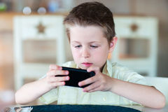 Boy playing on mobile phone Royalty Free Stock Images