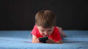 Boy playing on a mobile phone stock video footage
