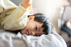 A kid is playing in the morning while watching TV in the bed in the bedroom royalty free stock photos