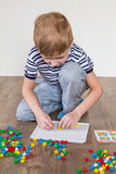 Boy playing in a mosaic. Boy playing puzzle sitting on the floor stock photography