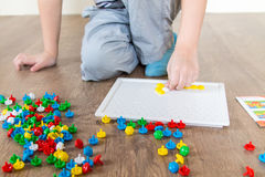 Boy playing in a mosaic. Boy playing puzzle sitting on the floor royalty free stock photography