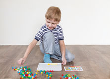 Boy playing in a mosaic. Boy playing puzzle sitting on the floor stock photos