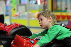 Boy playing with motorcycle simulator Royalty Free Stock Images