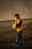 Boy playing in mud. Young boy playing in the mud with a ball stock photography