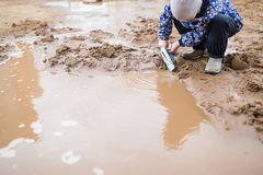 Boy playing in a muddy puddle royalty free stock photography