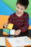 Boy playing with multicolored cubes Stock Photo
