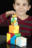 Boy playing with multicolored cubes Stock Photography