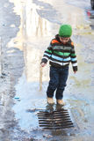 Boy playing near drainage Royalty Free Stock Photography