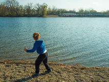 Boy playing near lake Royalty Free Stock Photography