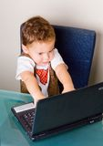 Boy playing with a notebook. Small boy playing with a black notebook computer Royalty Free Stock Image