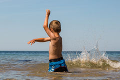 Boy playing in the ocean Stock Images