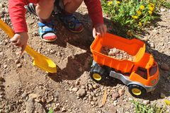 Boy playing with orange toy car stock photography