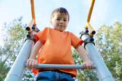 Boy playing outdoors on bar gym. Kid on playground,children activity. Child having fun. Active healthy childhood Stock Photos