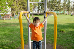 Boy playing outdoors on horizontal bar gym. Kid on playground,children activity. Child having fun. Active healthy childhood Stock Photo