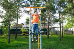 Boy playing outdoors on horizontal bar gym. Kid on playground,children activity. Child having fun. Active healthy concep Stock Image