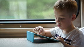 Boy playing on pad in the train trying to win. Little boy playing on touchpad in the train, at first he clapping getting success, then he trying to finish the stock footage