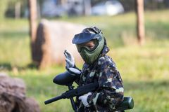 Boy is playing paintball on the field. paintball games can be played on indoor or outdoor fields stock image