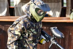 Boy is playing paintball on the field. paintball games can be played on indoor or outdoor fields royalty free stock images
