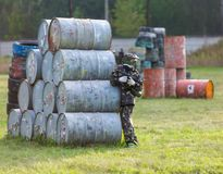 A boy is playing paintball on the field. two teams of paintball players in camouflage form with masks, helmets, guns on the field royalty free stock photos
