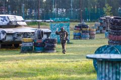 boy is playing paintball on the field. two teams of paintball players in camouflage form with masks, helmets, guns on the field royalty free stock photo