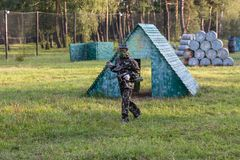 Boy is playing paintball on the field. two teams of paintball players in camouflage form with masks, helmets, guns on the field royalty free stock image